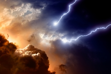 Dramatic sky with clouds backlit by fiery colors, black on the opposite side, with lightning bolts severing sky