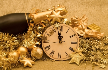 Champagne bottle resting on glittery gold stars and a clock face about to strike midnight
