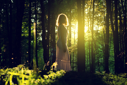 Young women standing in forest as sun breaks through the trees