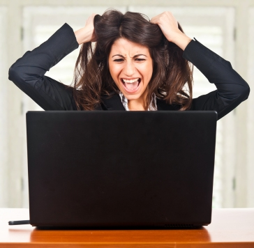 Woman sitting in front of laptop, gripping her hair and yelling
