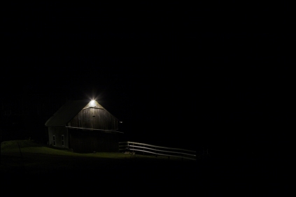 Barn at night with a light on