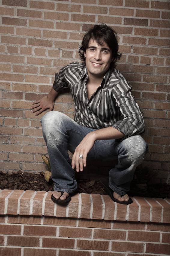 Handsome man squatting on a building garden ledge