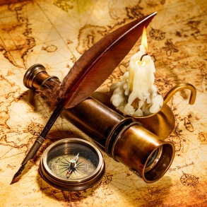 Vintage compass, spyglass, feather pen and candle on old see map