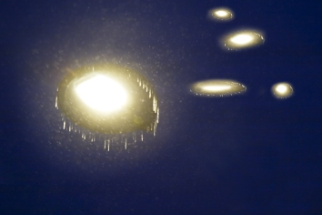 A dark night sky with several glowing discs of light