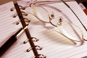open binder with lined paper, a pen and eye glasses resting on top