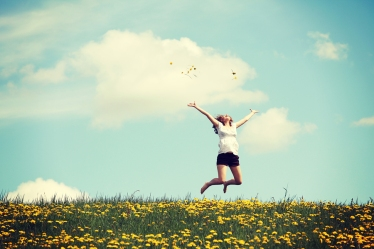 Happy woman jumping in a field of flowers