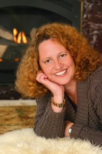 Casual photo of author Mindy Hardwick before a fireplace