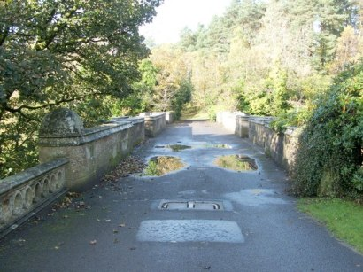 Looking across Overtoun Bridge. Stone bridge with greenery on either side, rain puddles in pathway
