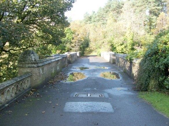 Looking across Overtoun Bridge. Stone bridge with greenery on either side, rain puddles in pathway