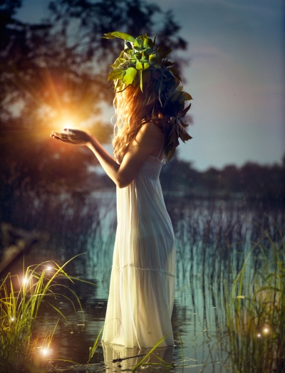 Fantasy girl taking magic light in her hands, standing on edge of pond at night