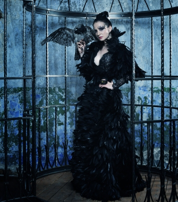 Gothic looking woman wearing a long back gown and holding a raven