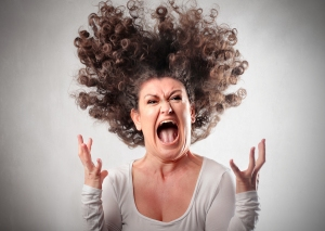 Very angry woman screaming with hair flying in the air