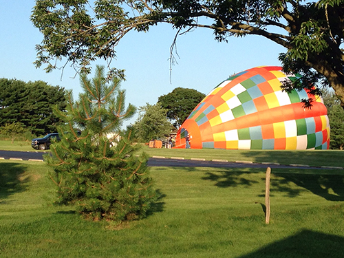 A colorful hot air balloon lying on its side and being filled with air