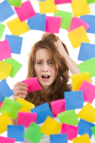 Stressed woman with pink note surrounded by colorful post-it reminders