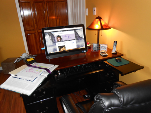 A writer's work space with desk and computer