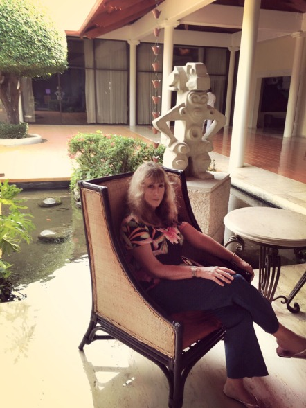 Author Mae Clair relaxing in a high backed chair