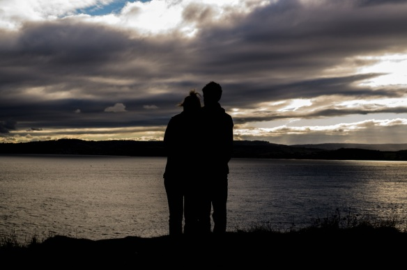 Silhouette of a couple embracing on the shore of a lake