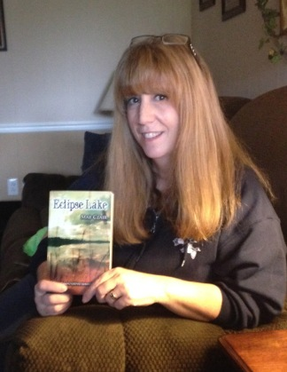 Author, Mae Clair holding a copy of her novel, Eclipse Lake