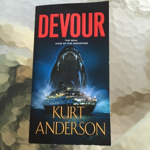 Book cover for DEVOUR by Kurt Anderson shows a cruise ship at night with lights and a huge monstrous mouth with teeth looming above it