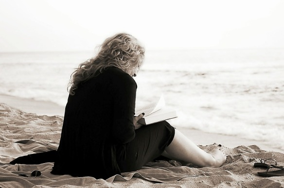 A woman sitting on the beach reading a book. Her back is to the camera, with ocean in front. Done in a wash of faded colors