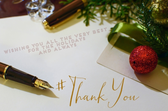 Holiday thank-you card surrounded by open fountain pen, and red and green decorations . Gold ink
