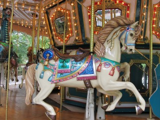 Brightly colored carousel horse on a lighted carousel