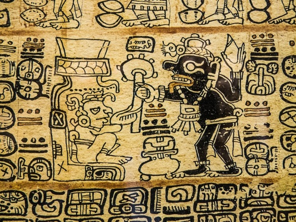 An Aztec drawing of figures in black on a gold background