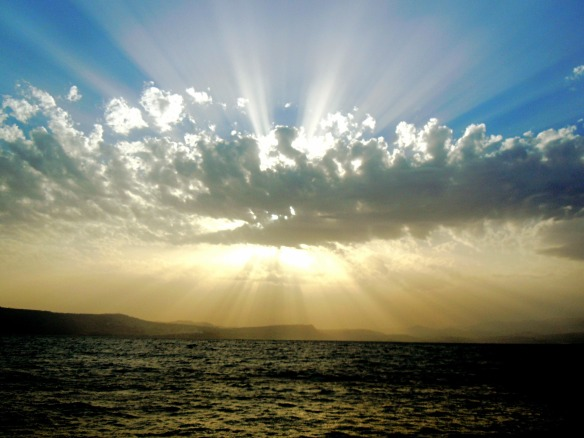 clouds with sun behind over ocean
