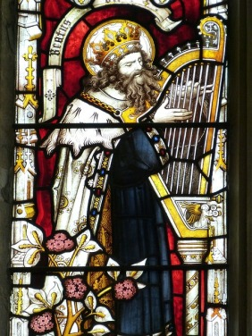 Stained glass image of King David with harp