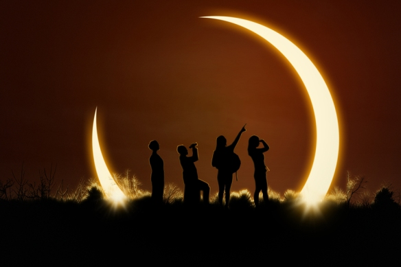 Silhouette of four people on a hillside watching a solar eclipse