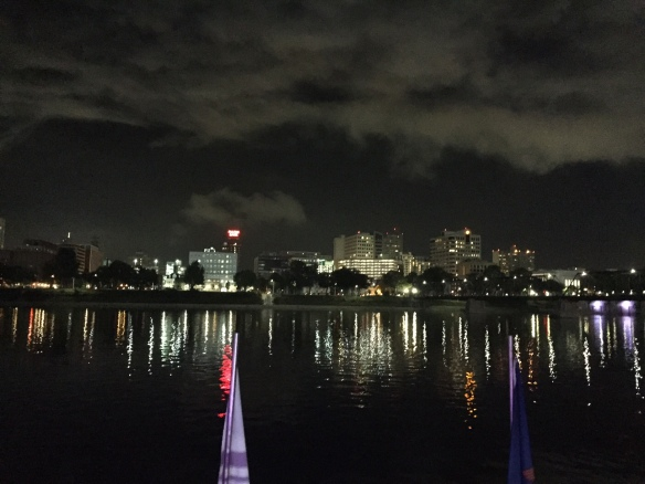 city skyline at night with reflections on river