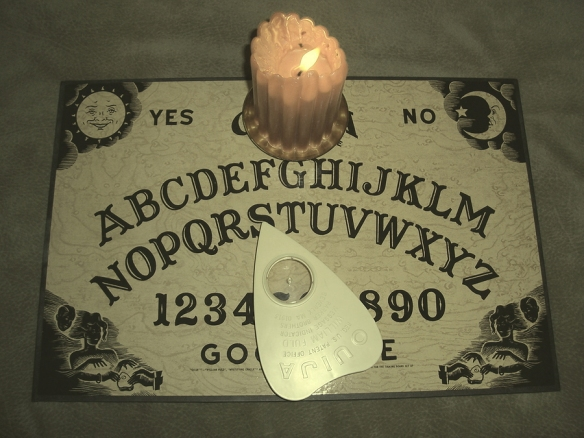 This is a Ouija board with lit candle on the antique setting.