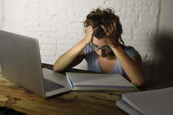 woman with glasses has head down, hands clasped in hair, looking exhausted. Open laptop and blank notebook on desk in front of her