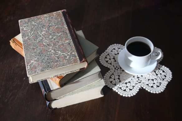 old books in a stack beside a cup of coffee on a lace doily