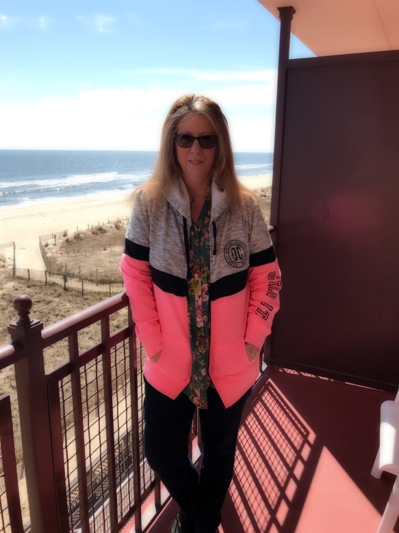 Mae Clair on standing on balcony with beach and ocean in backround