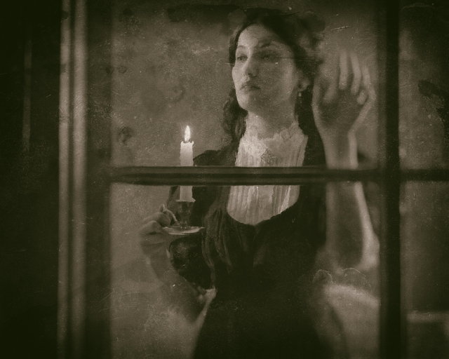 Victorian woman holding candlestick looking out rainy window.