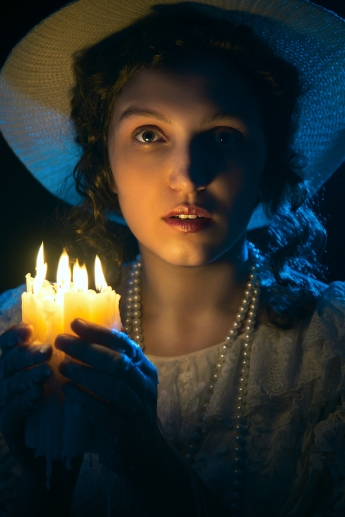 scared young woman in Victorian-era clothing holding candles