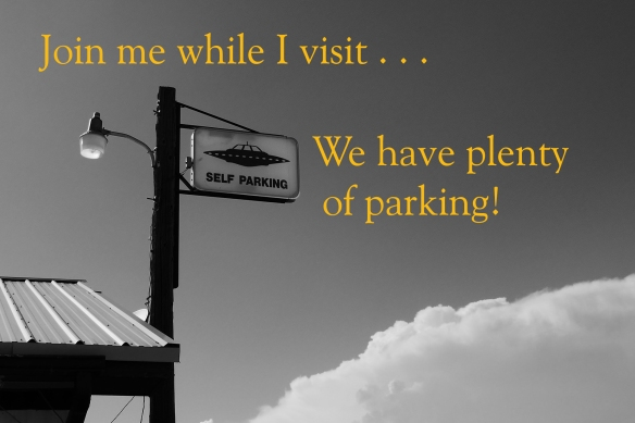 """""""Self parking"""" sign attached to a streetlamp beside a building. Flying saucer is pictured on sign"""