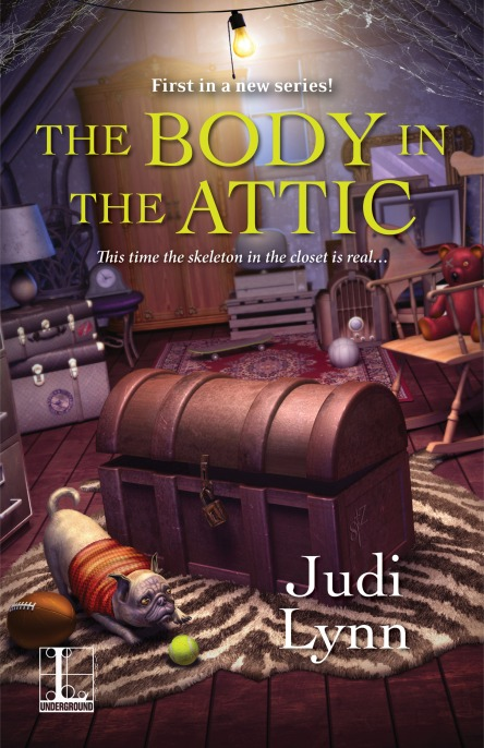 Book cover for the cozy mystery novel The Body in the Attic by Judi Lynn shows an old trunk surrounded by various items in an attic