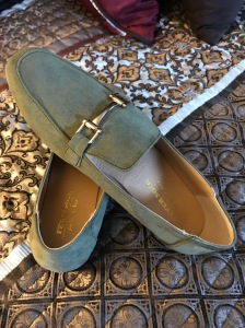 a pair of sage green women's loafers with gold embellishment across the bridge
