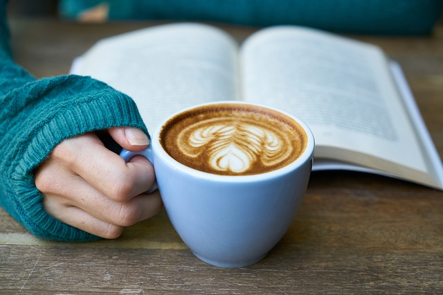 Open book, woman's arm in comfy sweater, she is holding a cup of coffee with a swirl of cream on top