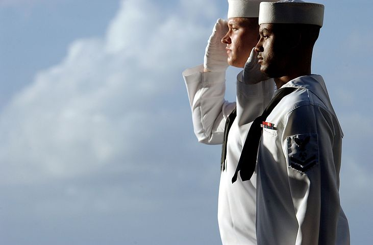 Two young men in naval uniforms, viewed from side, standing at attention and saluting