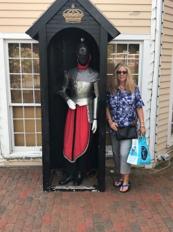 Author, Mae Clair, standing beside a full-size statue of a knight