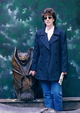 Early photo of author, Mae Clair standing beside a large wood carving of a bat with folded wings