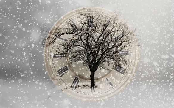 Old fashioned clock face surrounded by field of snow, bare tree superimposed over clock face