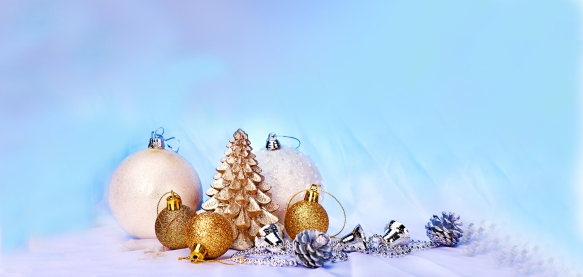 A collection of Christmas bulbs in white, gold and silver on a blue background. Also, small gold Christmas tree and silver bells