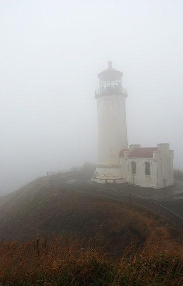 Lighthouse on rocky coast shrouded in dense fog