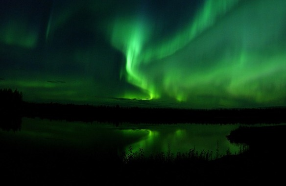 northern lights creating bands of green above lake in dark of night