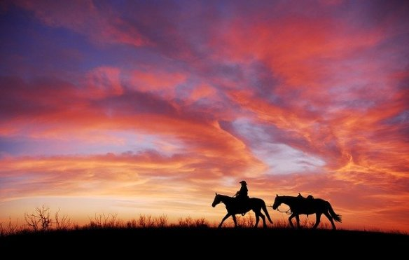Cowboy on a horse at sunset, leading a riderless horse behind him