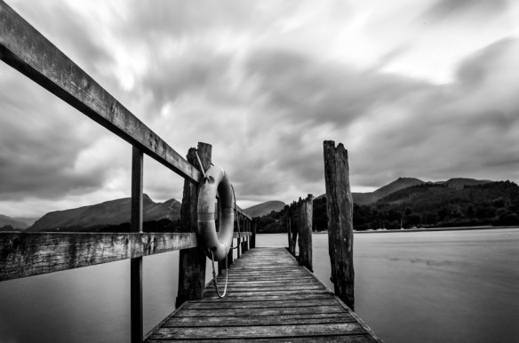 A wooden pier with a life preserver on the railing leads to a calm lake